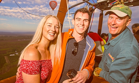 Hot Air Balloon pilot with happy passengers in basket smiling to camera